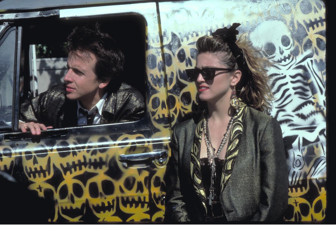 Robert Joys sitzt als Jim in einem schwarzen Kleinbus, während Madonna als Susan daneben steht in Susan... Verzweifelt Gesucht.