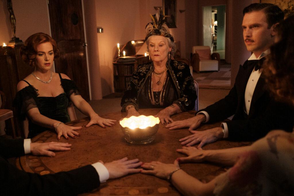 Charles (Dan Stevens) und seine Frau Ruth (Isla Fisher) haben eine private Séance bei Madame Arcati (Judi Dench) in Da scheiden sich die Geister. Sie sitzen im Kreis an einem Holztisch. Es ist dunkel und in der Mitte des Kreises steht ein Licht.