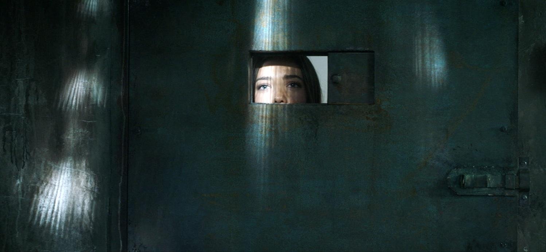 Zoe (Jemma Dallender) beobachtet durch einen kleinen Schlitz in der Tür ihren Vater beim Foltern zu
