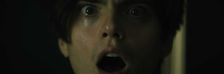Luke (Miles Robbins) kämpft in Daniel Isn't Real mit seinem inneren bösen Dämon. Das zeigt sich hier in einem intensiven Gesichtsausdruck mit weit aufgerissenem Mund und entsetzten Augen.