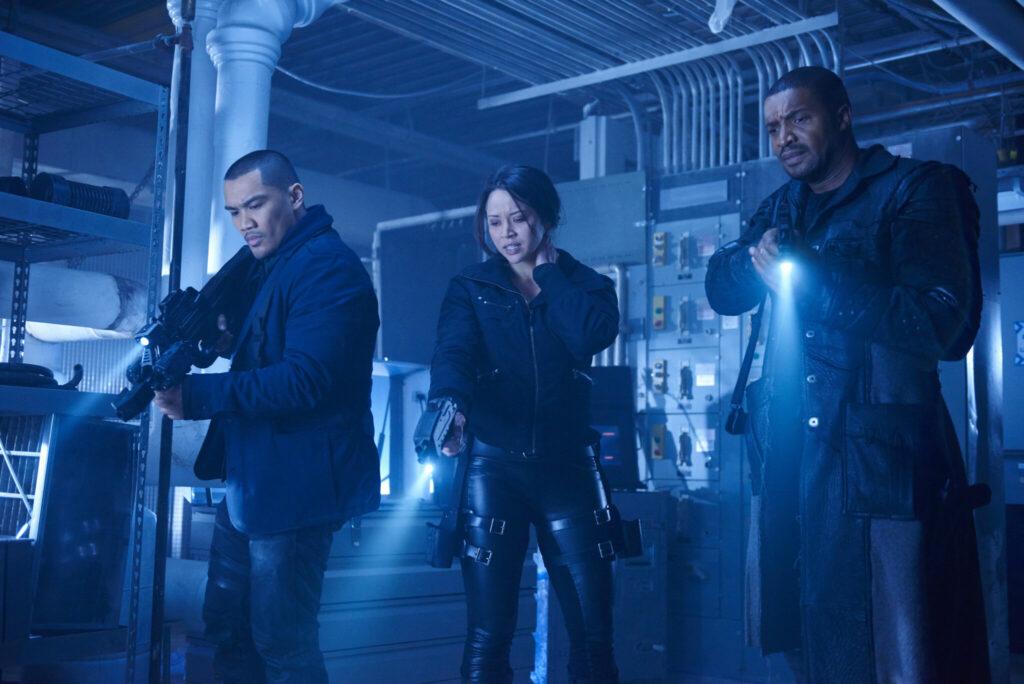 Vier, gespielt von Alex Mallari Jr., Zwei, gespielt von Melissa O'Neil, und Sechs, gespielt von Roger Cross, haben ihre Schusswaffen im Anschlag.