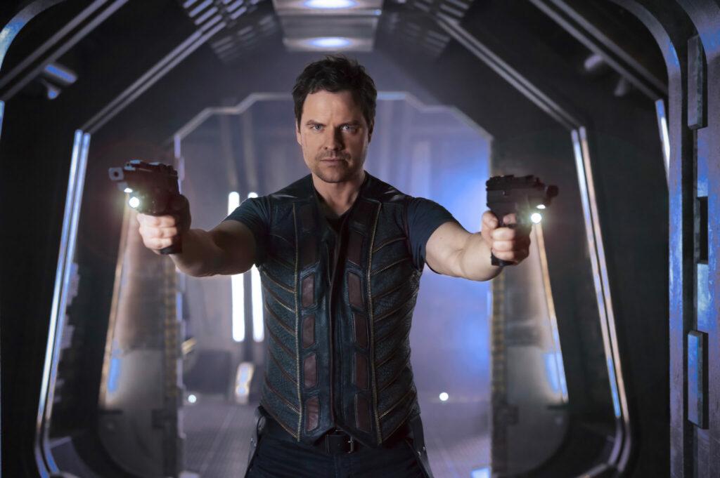 Drei, gespielt von Anthony Lemke, hat in Dark Matter zwei Schusswaffen auf einen Gegner angelegt.