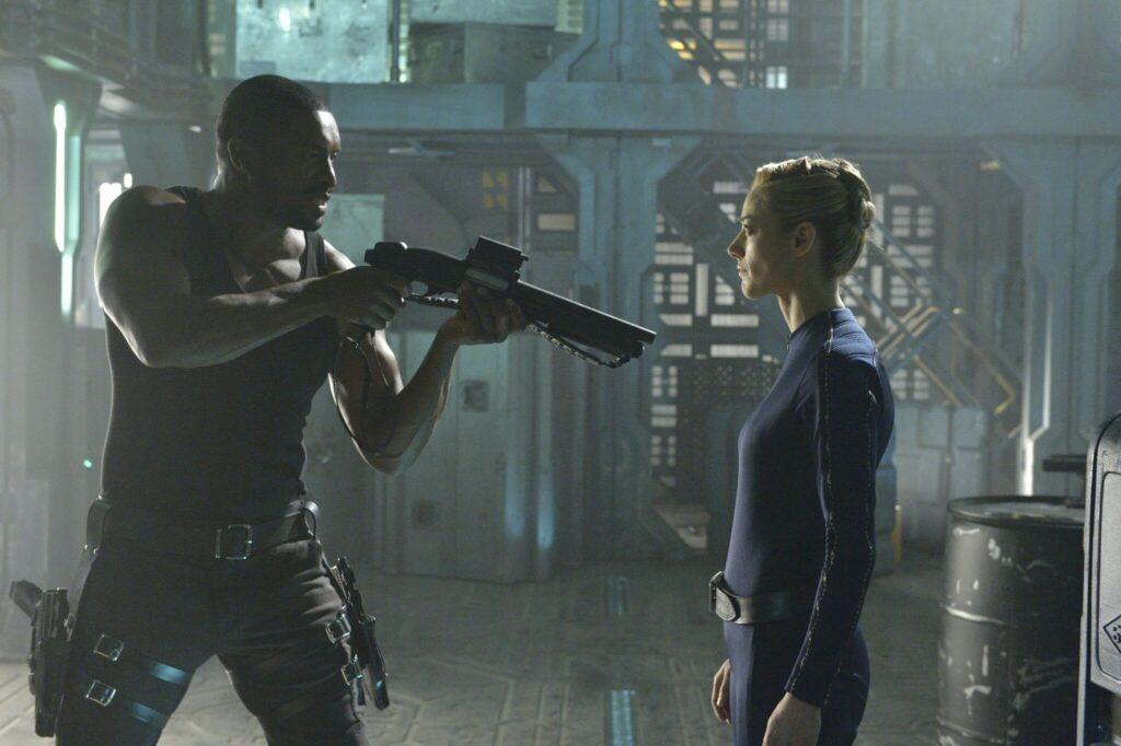 Sechs, gespielt von Roger Cross, muss sich anfangs gegen die Androidin, gespielt von Zoie Palmer, verteidigen. Er hält sie mit einem Gewehr in Schach.