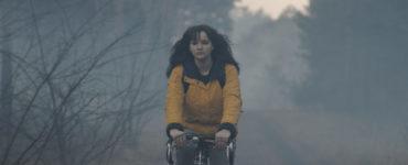 Lisa Vicari spielt Martha Nielsen in allen Staffeln der Dark Serie. Sie trägt einen gelben Regenmantel und fährt auf einem Fahrrad durch den Wald. Es wirkt etwas nebelig.