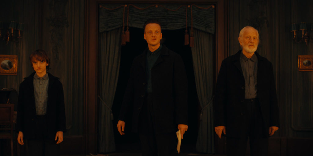 Bei diesem Bild stehen drei männliche Personen in jeweils schwarzer Kleidung in einem dunklen Raum und blicken auf etwas helles, dass vermutlich einem Feuer entspringt. Alle drei sind unterschiedlichen Alters, von links nach rechts sind es ein Junge von vielleicht acht Jahren, ein erwachsener Mann um die vierzig Jahre, und ganz rechts ein noch älterer Herr mit weißen Haaren und Vollbart. Der Mann in der Mitte hält in seiner linken Hand Papiere.