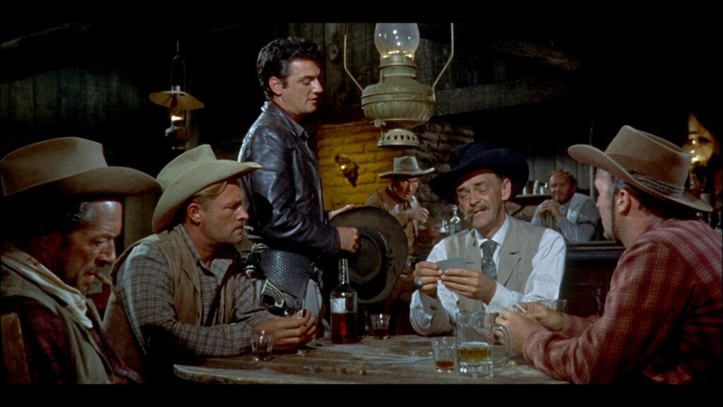 Jim Bonniwell, gespielt von John McIntire, sitzt am Pokertisch, Johnny Ringo, gespielt von William Campbell, steht daneben und beobachtet ihn.