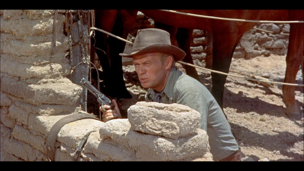 Jim Slater, gespielt von Richard Widmark, geht im Showdown von Das Geheimnis der fünf Gräber hinter einer bröckeligen Mauer in Deckung.