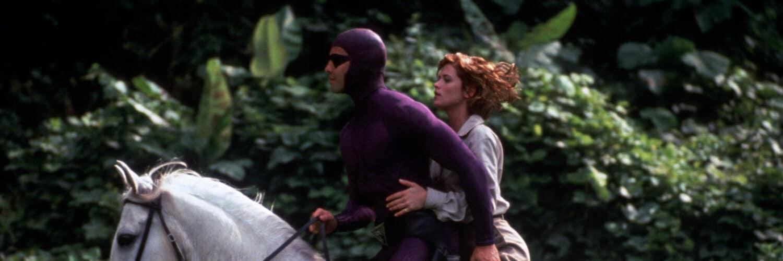 Billy Zane alias Das Phantom reitet auf einem weißen Pferd, hinter ihm sitzt Kristy Swanson in einem beigefarbenen Abenteureroutfit und schulterlangen rotbraunen Haaren. Im Hintergrund ist der Dschungel zu sehen.