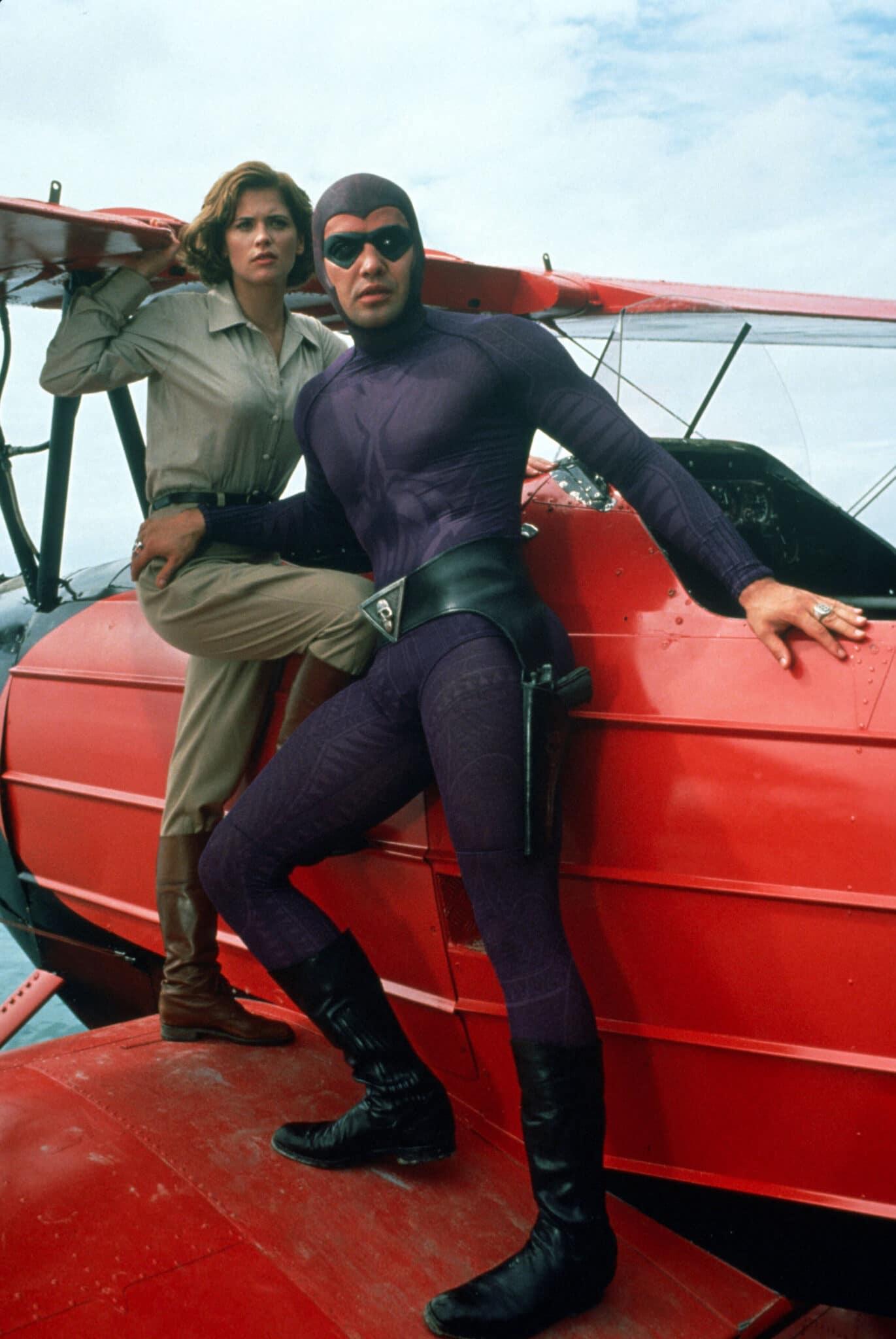 Billy Zane als Das Phantom steht mit Kristy Swanson auf dem Flügel eines roten Kleinflugzeugs. Beide wirken angespannt und bereit zum Sprung.