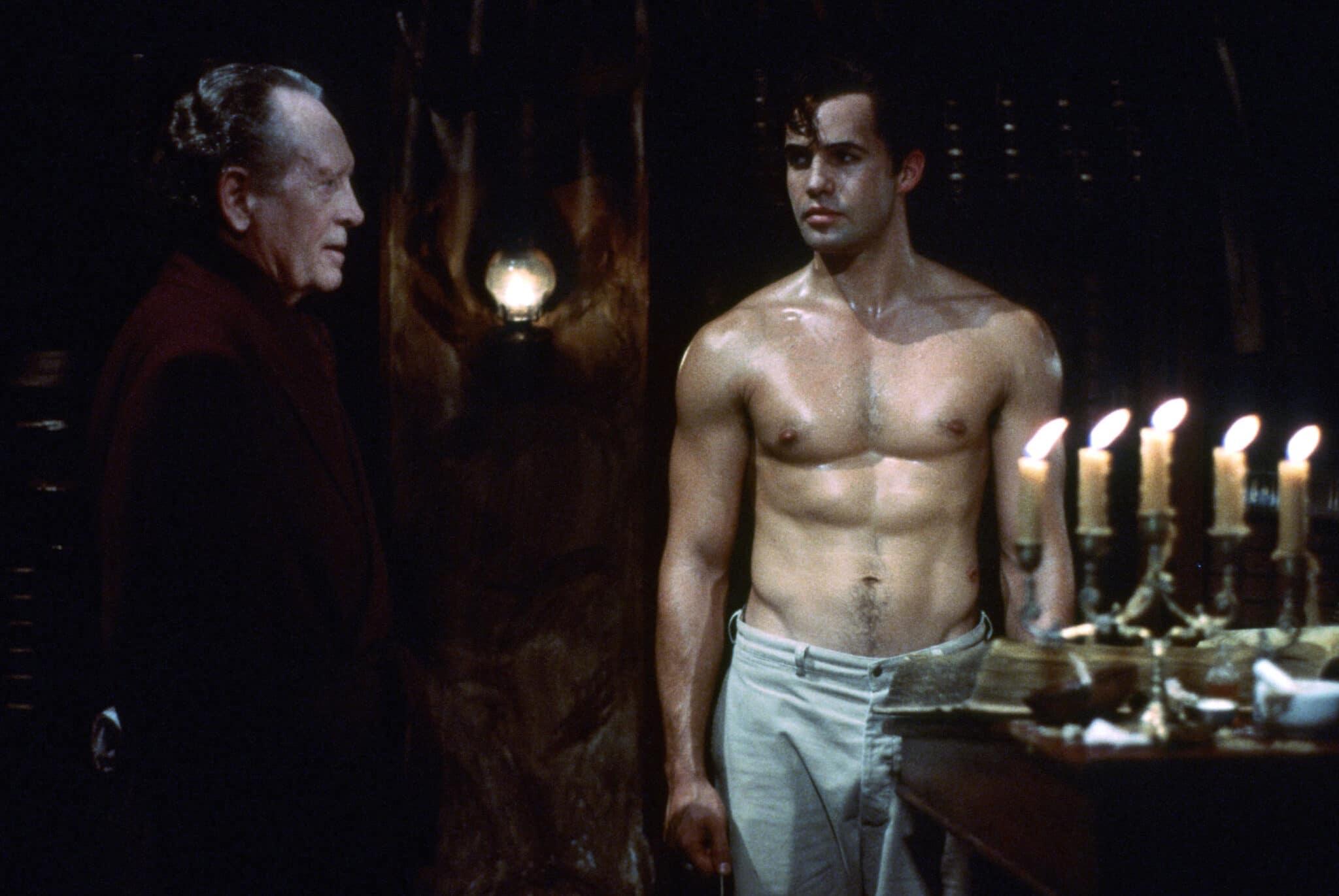 Billy Zane alias Das Phantom steht oberkörperfrei in seinem Höhlenunterschlupf, die nur von Kerzenlicht beleuchtet ist. Er wirkt verschwitzt und redet gerade mit einem älteren Mann.