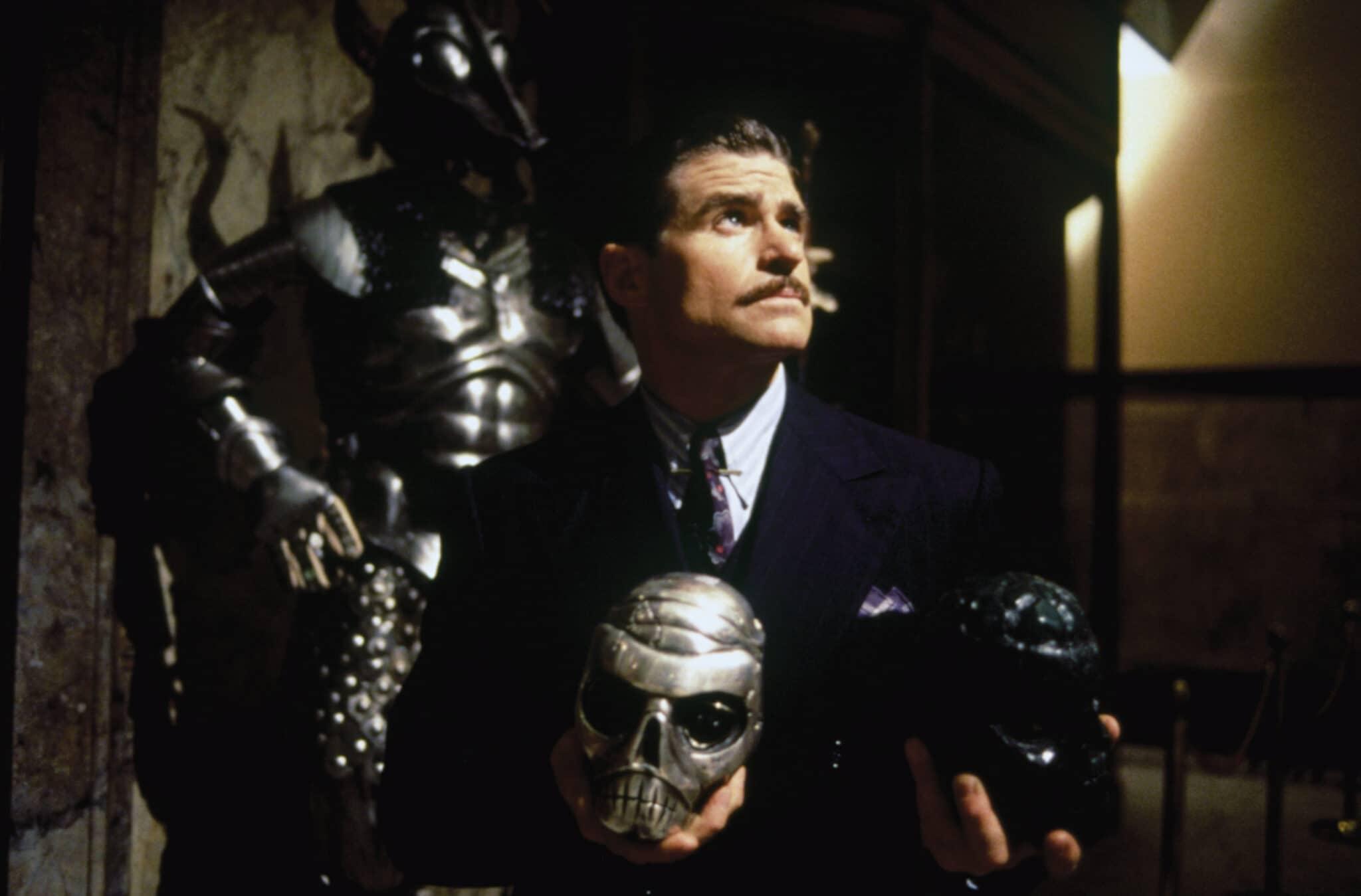 Treat Williams spielt den Bösewicht Xander Drax in Das Phantom. Er trägt einen schwarzen Anzug mit Krawatte, kurze Haare und einen Schnauzbart. In den Händen hält er einen silbernen und schwarzen Totenkopf aus Metall, im Hintergrund sind alte Rüstungen in einem Museum zu sehen.