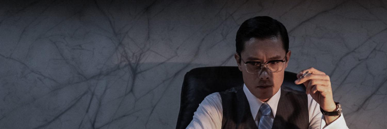 Direktor Kim (Lee Byung-hun) sitzt in Das Attentat - The Man Standing Next nachdenklich und rauchend in seinem Büro, vor ihm stehen zwei Telefonapparate mit Wählscheibe.