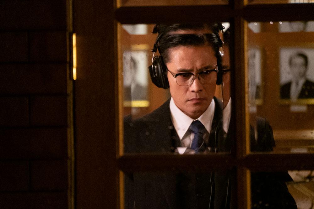 Protagonist Kim (Lee Byung-hun) steht in Das Attentat - The Man Standing Next hinter einer verglasten Tür und folgt mit aufgesetzten Kopfhörern aufmerksam einem Gespräch.