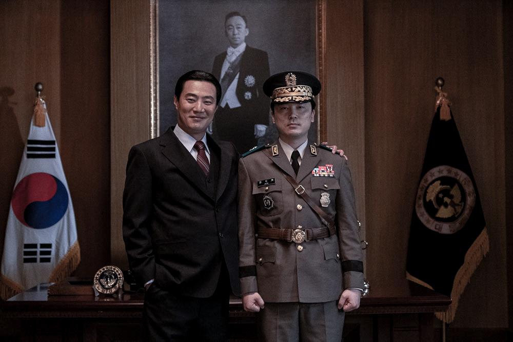 Sicherheitsleiter Kwak Sang-cheon (Lee Hee-joon) steht in Das Attentat - The Man Standing Next lächelnd neben dem ernst drein blickenden Militärchef Chun Doo-hyeok (Seo Hyun-woo). Im Hintergrund ist ein großes Gemälde von Präsident Park zu sehen.