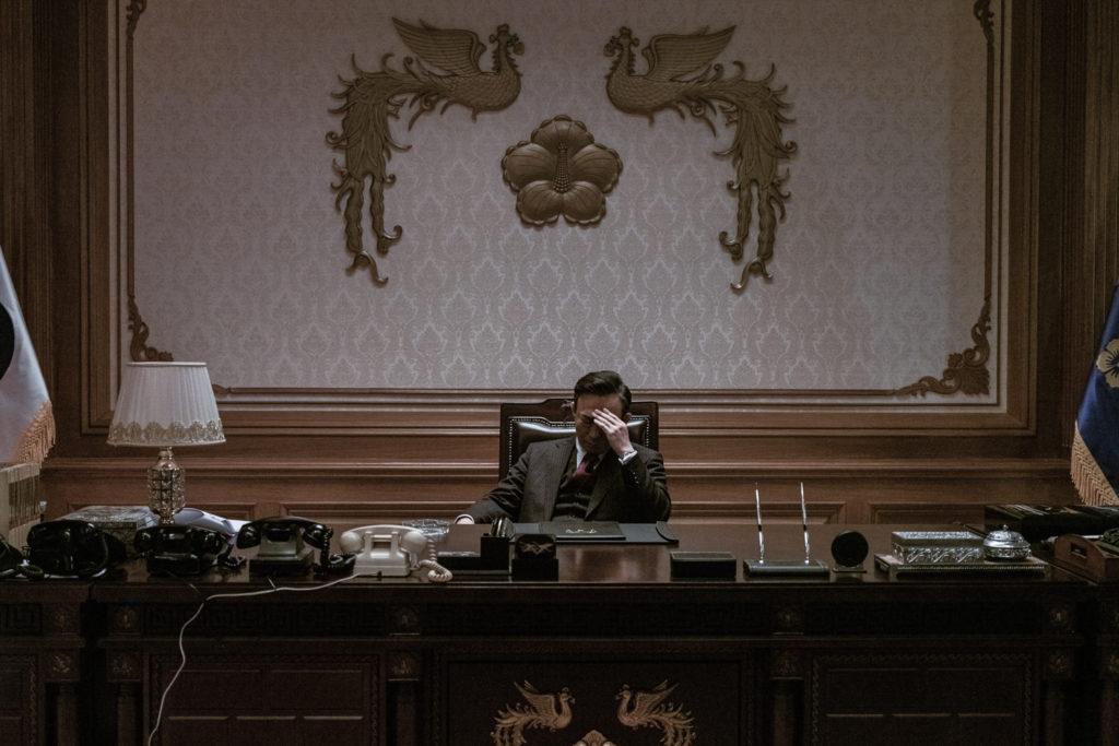 Präsident Park (Lee Sung-min) sitzt in Das Attentat - The Man Standing Next in seinem großräumigen Büro vor aufgeräumtem Schreibtisch und grübelt, die Hand vor dem Gesicht.