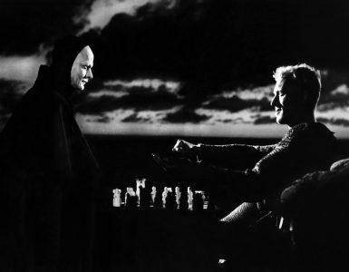 Der Tod (Bengt Ekerot) sitzt links im Bild und spielt Schach mit A dem ihm gegenüber sitzenden Antonius Block (Max von Sydow). Im Hintergrund ballen sich dunkle Wolken am Himmel.