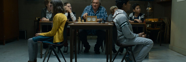 Fahim, gespielt von Assad Ahmed, und seine Klubfreundin Luna, gespielt von Sarah Touffic Othman-Schmitt, sitzen mit den Rücken zum Schachbrett. Sie trainieren, Schach blind zu spielen.