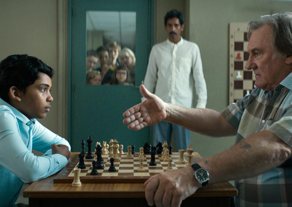 Fahim (Assad Ahmed) sitzt Sylvain (Gérard Depardieu) am Schachbrett gegenüber. Der Trainer reicht ihm die Hand. Im Hintergrund steht Fahims Vater Nura