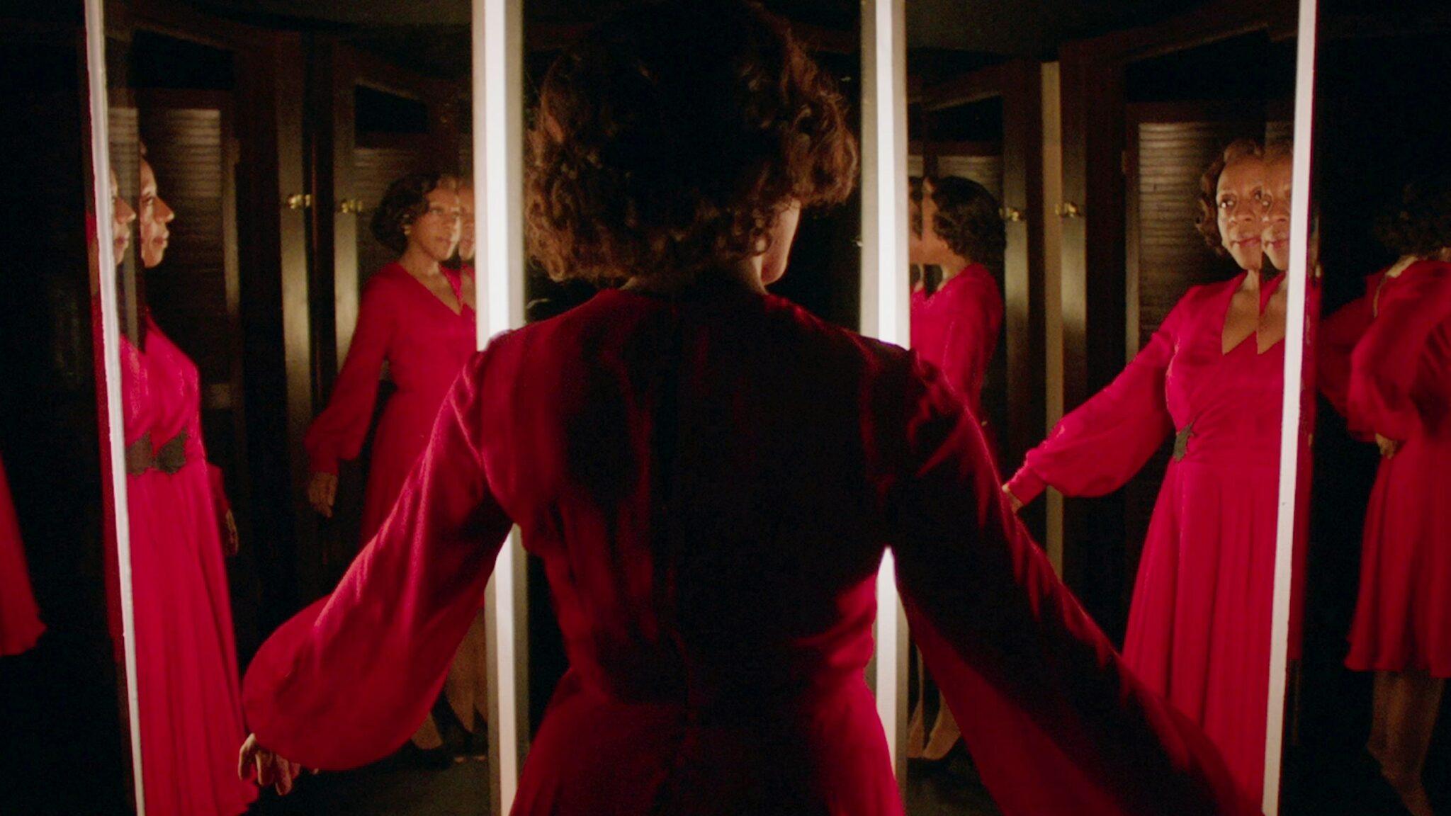 Sheila (Marianne Jean-Baptiste) steht in einem Raum voller Spiegel und trägt das blutrote Kleid.