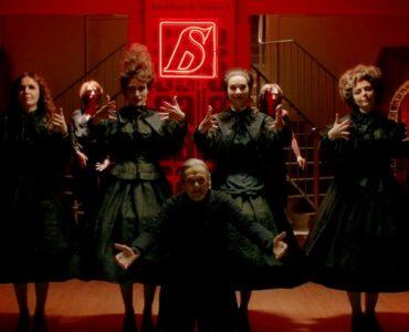 Die Belegschaft eines Modehauses steht aufgereiht vor einer Neonleuchte. Alle tragen dunkle Kleidung und auffällige Frisuren.
