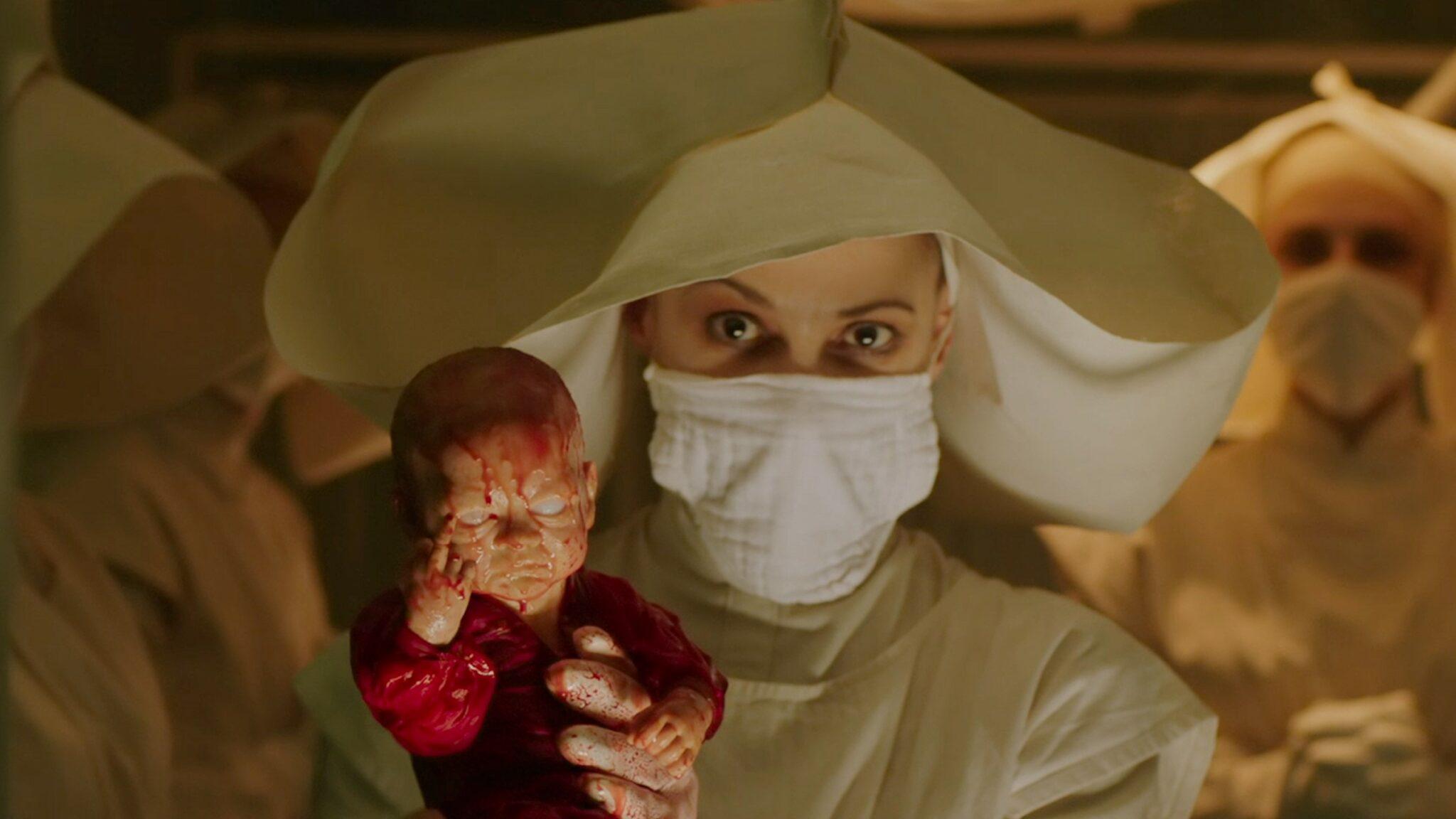 Eine Frau in weißem Gewand mit weißer Haube und Mundschutz hält eine Puppe voller Blut in ihren Händen.