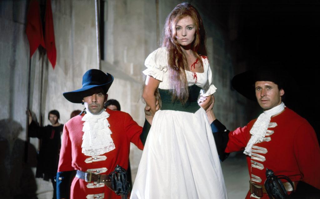Eine Frau wird als Gefangene vorgeführt, zwei Wachen halten sie an den Armen fest, von ihrem Kopf läuft Blut hinunter, im Hintergrund stehen Fahnenträger vor einer grauen Mauer