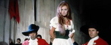 Alicia wird als Gefangene vorgeführt, zwei Wachen halten sie an den Armen fest, von ihrem Kopf läuft Blut hinunter, im Hintergrund stehen Fahrenträger vor einer grauen Mauer