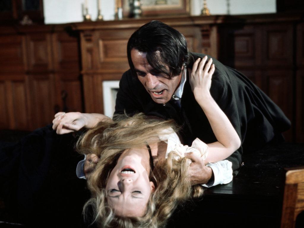 Mary wird von einem Mann gewaltsam mit dem Rücken auf einen Tisch gedrückt, ihr Gesicht ist qualvoll verzerrt, im Hintergrund ein Kamin