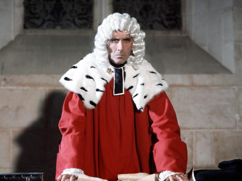 Lee steht in Der Hexentöter von Blackmoor als Jeffreys in seinem Richterkostüm mit Perücke auf den Tisch gestützt mit ernstem Blick