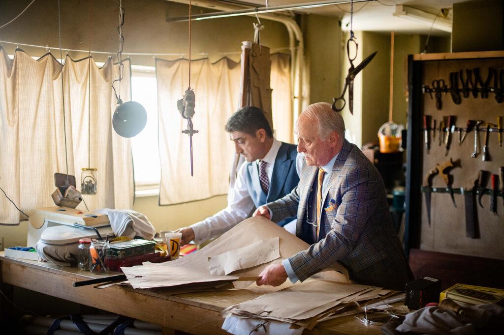 Nikos und sein Vater Thanasis stehen in ihrer Schneiderei am Arbeitstisch und betrachten neue Entwürfe - Der Hochzeitsschneider von Athen