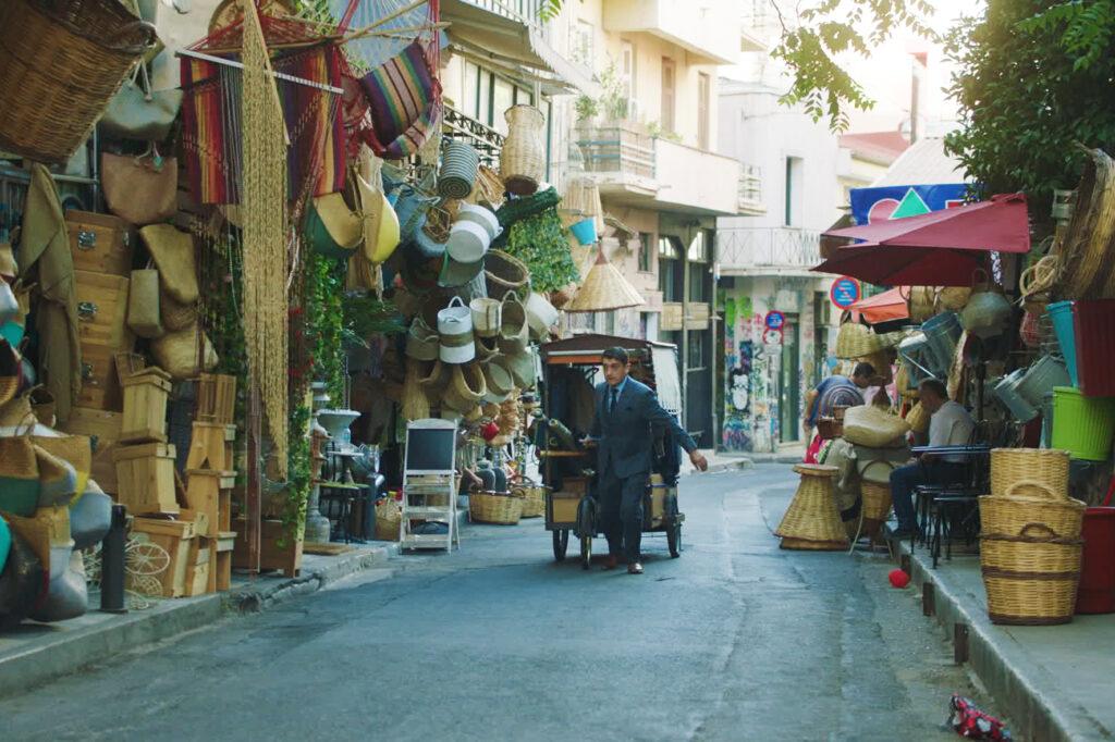 Nikos zieht mit mobilem Verkaufsstand durch die enge Ladengasse Stadt - Der Hochzeitsschneider von Athen