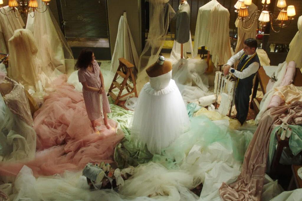 Olga und Nikos betrachten in dem einem Meer von Stoffresten gleichenden Verkaufsraum das fertige Hochzeitskleid - Der Hochzeitsschneider von Athen
