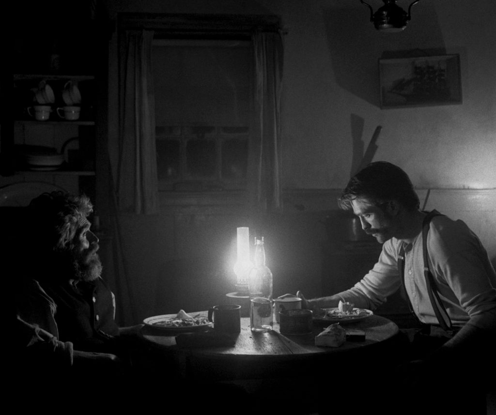 Thomas Wake (Willem Dafoe) und Ephraim Winslow (Robert Pattinson) sitzen am Tisch schweigsam beisammen.