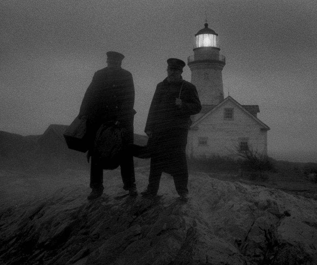 Thomas Wake (Willem Dafoe) und Ephraim Winslow (Robert Pattinson) warte im Sturm mit gepackten Sachen darauf, dass ihr Schiff sie endlich von der verfluchten Insel abholt.