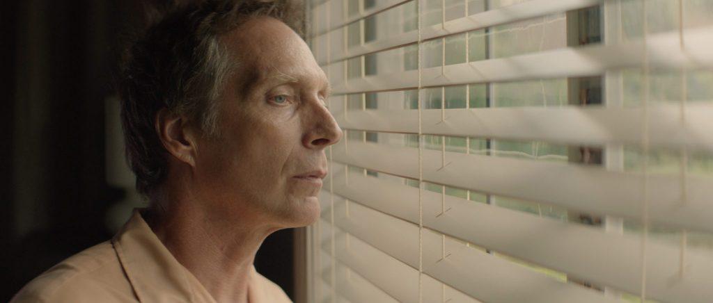 Mike (William Fichtner) beim heimlichen Beobachten seiner hübschen Nachbarin in Der Nachbar - Die Gefahr lebt nebenan. © Tiberius Film