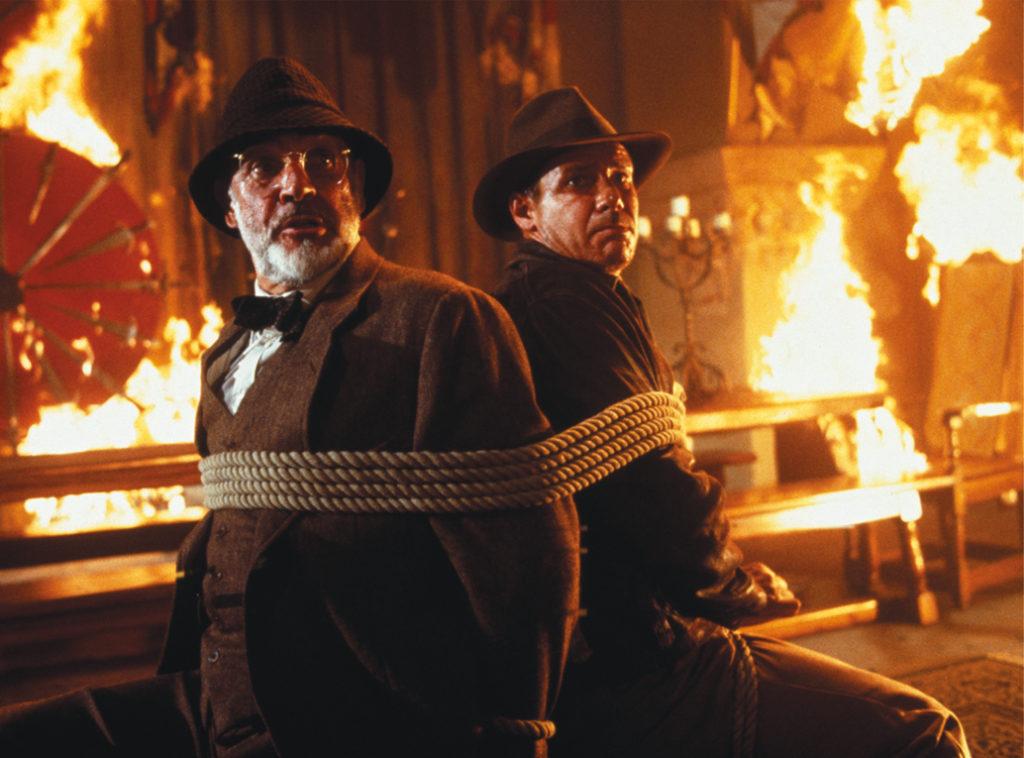 Harrison Ford und Sean Connery sind auf einen Stuhl gefesselt.