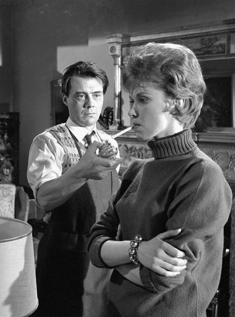 Susan, gespielt von Wendy Craig, lässt sich in der Diener von Hugo, gespielt von Dirk Bogarde, Feuer für ihre Zigarette geben.