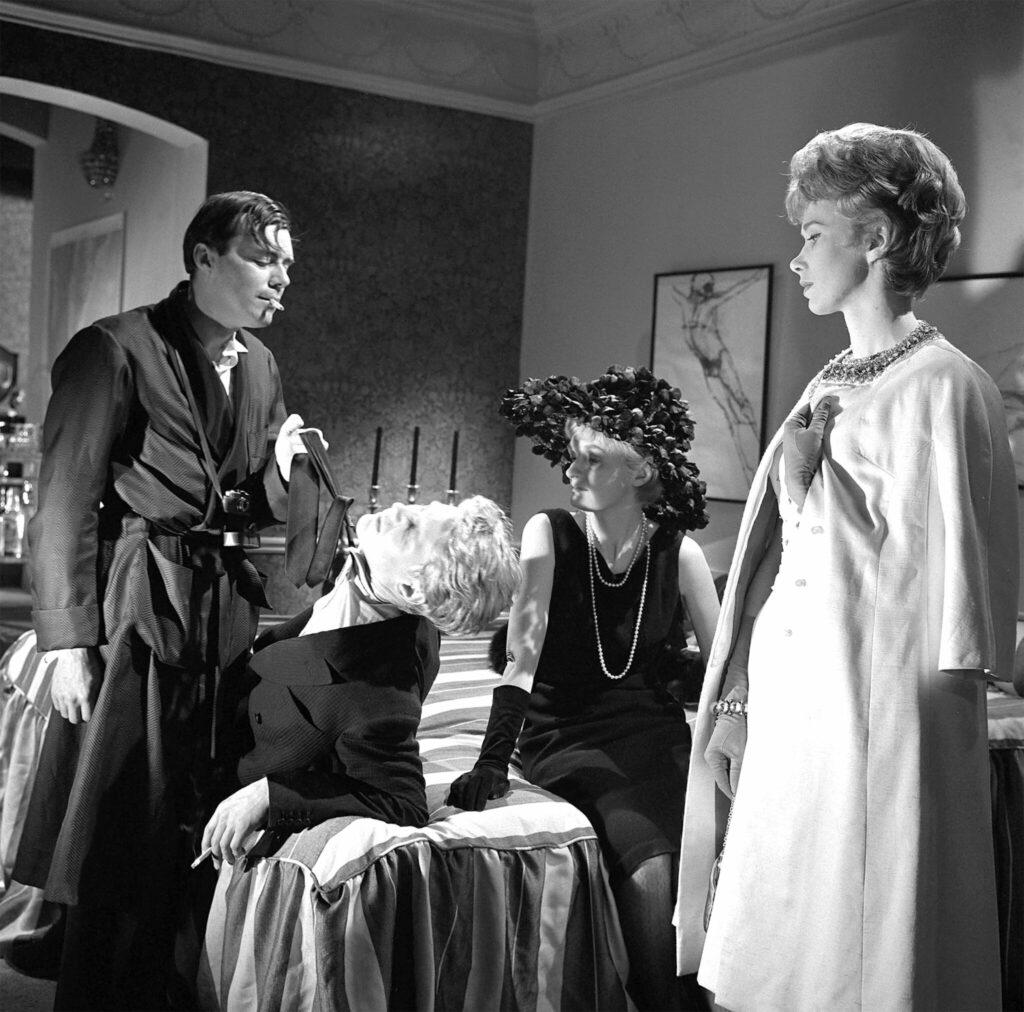 Hugo, gespielt von Dirk Bogarde, wie der Herr des Hauses mit einem Morgenmantel bekleidet und rauchend, hat in Der Diener den halb auf dem Bett liegenden Tony, gespielt von James Fox, an der Krawatte gepackt und demütigt ihn vor den Augen Susans, gespielt von Wendy Craig, und einer Unbekannten, die als Gast an der Party teilnimmt.