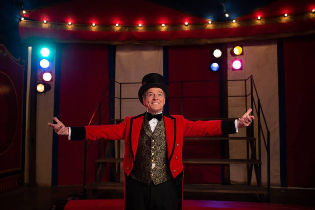 """Bryan Cranston spielt den Zirkusbesitzer Mack in """"Der einzig wahre Ivan"""". Dieser steht mit zur Seite ausgestreckten Armen in einer für einen Zirkusdirektor typischen Garderobe. Dieses besteht aus einer goldverzierten Weste, einem roten und hinten langen Frack, sowie einem schwarzen Zylinder. Im Hintergrund ist eine leere Tribüne zu sehen."""