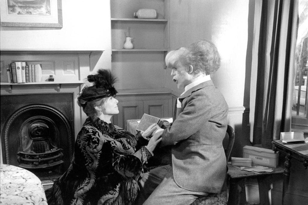 Mrs. Treves kniet im opulenten Mantel vor Merrick und hält seine Hand, während sie Romeo und Julia zitiert