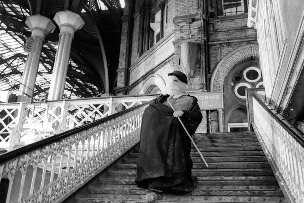 John Merrick, Der Elefantenmensch, geht eine öffentliche Treppe herunter. Sein Gesicht ist mit einer Art Tuch bedeckt.