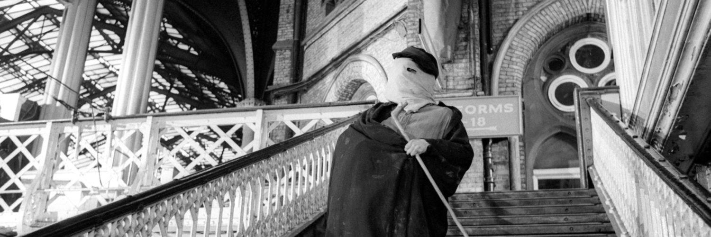 John Marrick, der Elefantenmensch, geht eine öffentliche Treppe herunter. Sein Gesicht ist mit einer Art Tuch bedeckt.