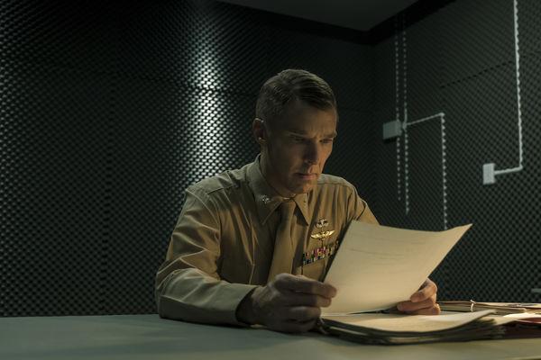 """Cumberbatch als Militäranwalt der Klage sitzt in einer dunklen und unterkühlt wirkenden Raum an einem Tisch. Er liest sich mehrere Dokumente durch. - """"Der Mauretanier"""""""