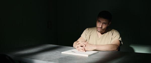 """Slahi (Tahar Rahim) sitzt an einem Tisch in einem dunklen Raum. Die Hände sind zusammengefaltet und liegen auf einem Papierblock. Er blickt außerhalb des Bildes zur einzige Lichtquelle. - """"Der Mauretanier"""""""