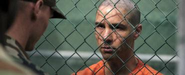 """Slahi (Tahar Rahim) steht in seiner orangenen Gefängniskleidung hinter einem Zaun und blickt ernst auf einen Soldaten, der auf der anderen Seite des Zauns steht und mit ihm scheinbar spricht. - """"Der Mauretanier"""""""