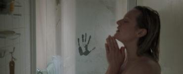 Protagonistin Cecilia (Elisabeth Moss) genehmigt sich eine warme Dusche, ihre Augen sind dabei geschlossen. Neben ihr ist ein Handabdruck an der beschlagenen Duschkabine zu sehen - der Unsichtbare beobachtet sie.