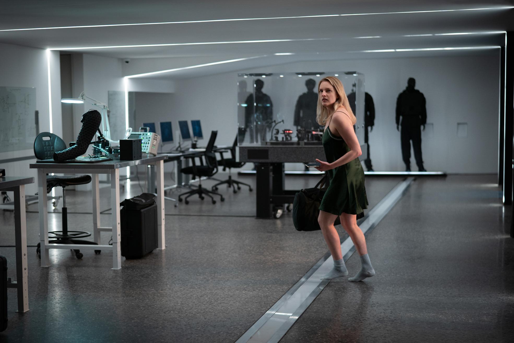 Cecilia (Elisabeth Moss) eilt in Der Unsichtbare im Nachthemd durch das Haus von Adrien, um ihm zu entkommen. Im Hintergrund sind einige Hightech-Geräte des anerkannten Wissenschaftlers zu erkennen.
