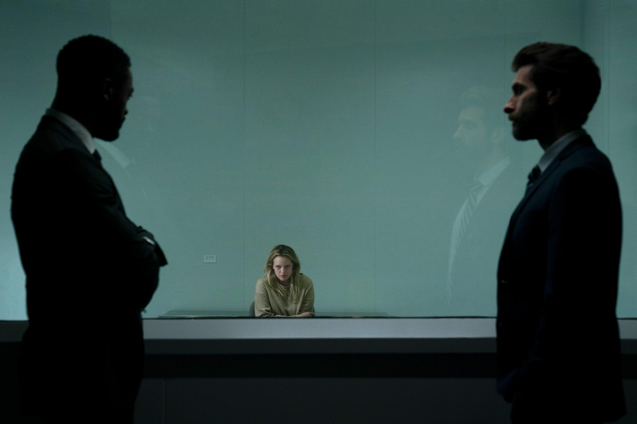 """Polizist und Freund James (Aldis Hodge) steht mit einem Kollegen vor der Fensterwand zum Verhörsaal, in dem Cecilia (Elisabeth Moss) sitzt. Niemand glaubt ihre Version mit """"dem Unsichtbaren""""."""