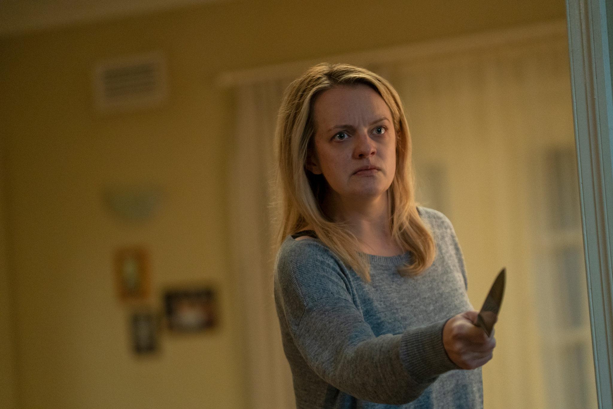 Cecilia (Elisabeth Moss) steht im grauen Pulli in einem gelb gestrichenen Zimmer und bedroht mit verzweifeltem und wütdendem Blick, bewaffnet mit einem Messer, einen Unsichtbaren.