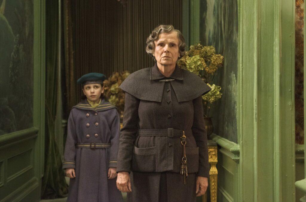 Mary, gespielt von Dixie Egerickx, wird in Der geheime Garten von Mrs. Medlock, gespielt von Julie Walters, durch das dunkle Haus geführt.